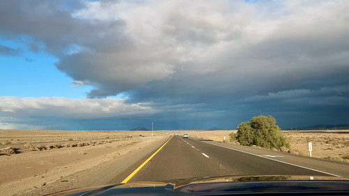 Beams of sunlight penetrating storm clouds and illuminating the Mojave Desert | by Parkzer
