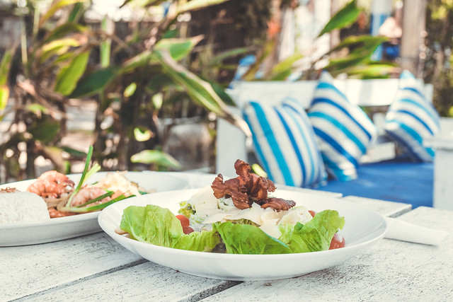 Caesar Salad on a white wooden table in the beach cafe, Bali island.