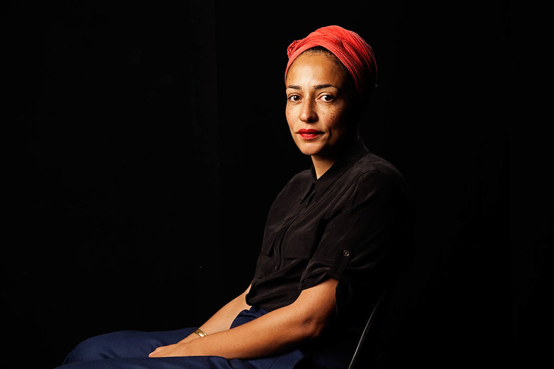 A portrait of a young woman, author Zadie Smith, sitting with a black background, looking at the camera.