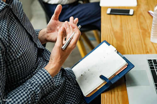 Man reading from his agenda | by Rawpixel Ltd