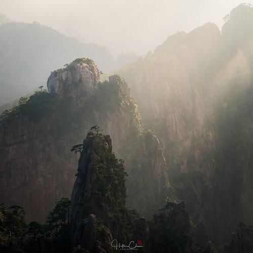 autumn anhuiprovince dwarfpines foggy lightbeams landscape huangshannationalpark granitepeaks sunrise misty china yellowmountains huangshancity anhui cn