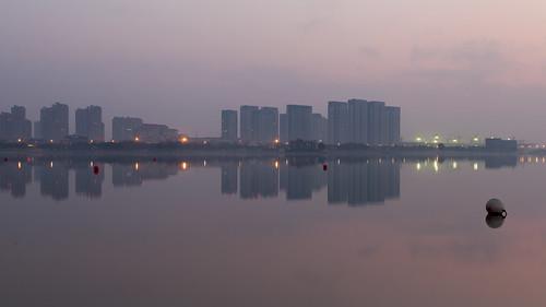 yixing wuxi jiangsu china prc sunrise dawn softlight water reflections calm mirror dongjiu lake highrise skyscrapers buildings city architecture tall pink sky