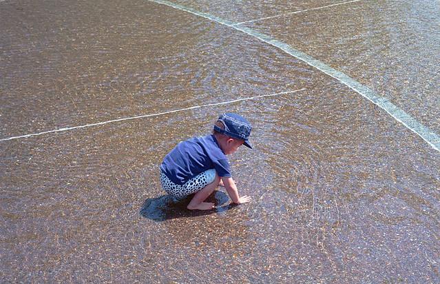 浅い水辺に手を浸す子。