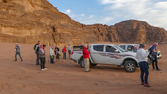 Tourists looking at the setting sun in the Wadi Rum desert