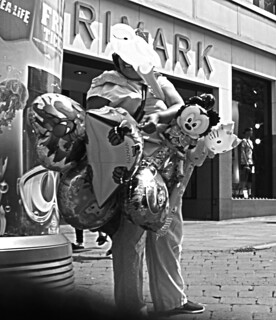 BALLOON LADY STANDING SELLING HER NOVELTY BALLOONS IN AN EAST LONDON BOROUGH SUBURB MARKET TOWN STREET ENGLAND BLACK AND WHITE PHOTO SS855137 BW