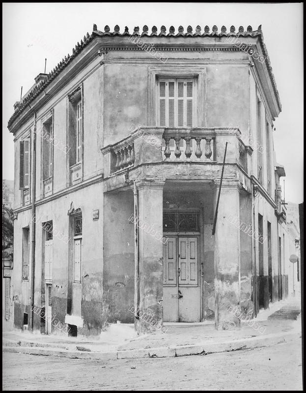 """Κτίριο στη συμβολή των οδών Μαίζωνος και Μαδύτου, Πειραιάς. Φωτογραφία του Στέλιου Σκοπελίτη από το βιβλίο """"Νεοκλασσικά σπίτια της Αθήνας και του Πειραιά"""" Εκδόσεις """"Δωδώνη"""", Αθήνα, 1975."""