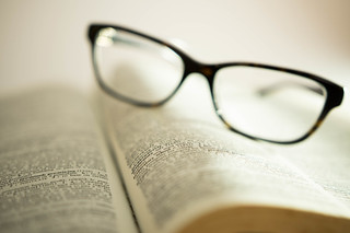 Words focused on a book with reading glasses on the background | by wuestenigel