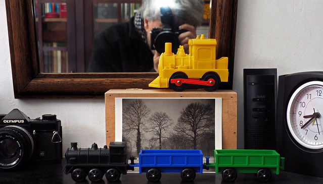 Plastic toy trains and other stuff on my mantelpiece
