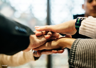 Diverse people stacking hands together | by Rawpixel Ltd
