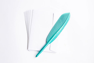 Top view of white envelopes with blue plastic feather pen on white background   by wuestenigel