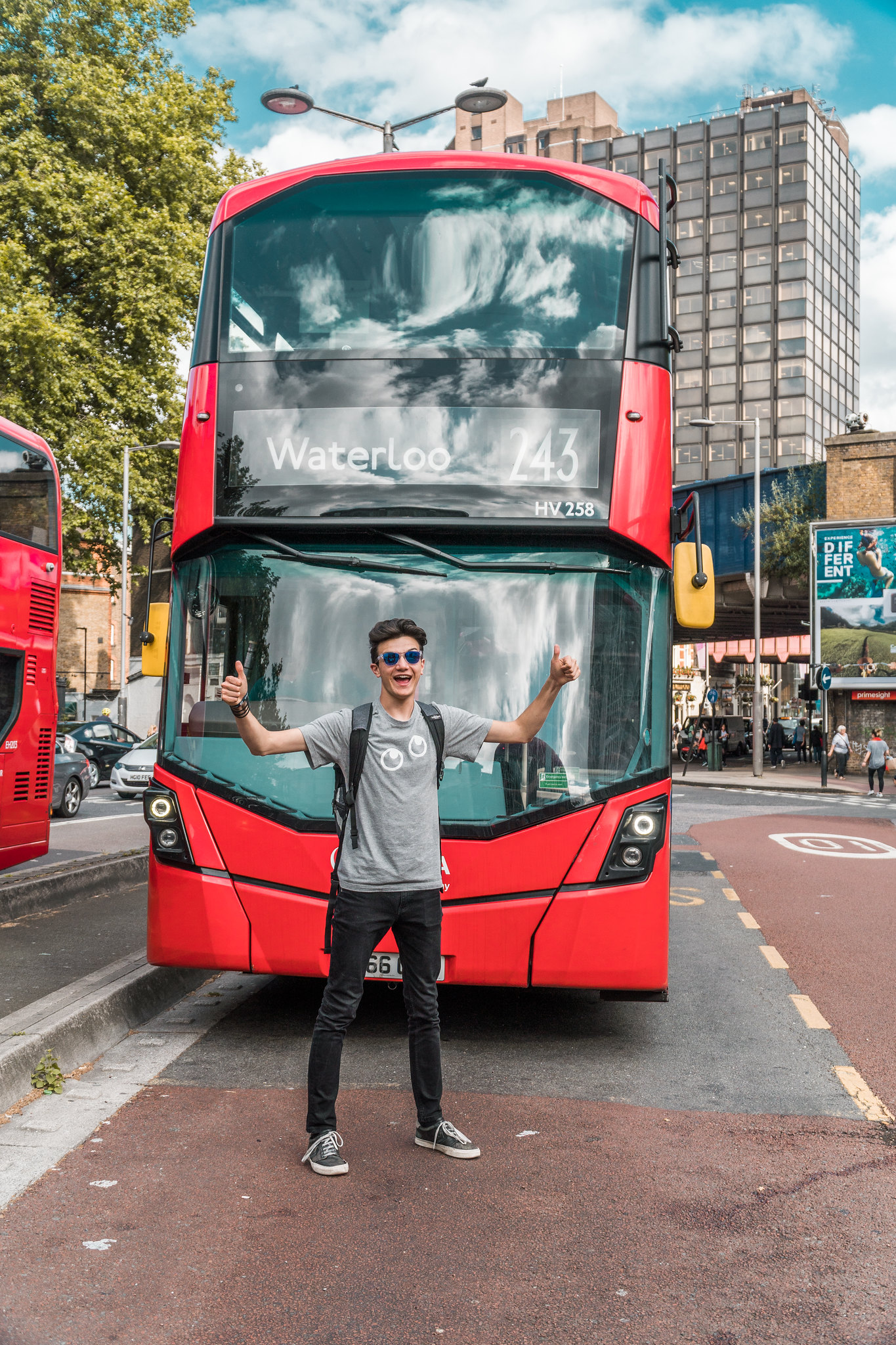 Tommi fa il figo davanti a un bus a due piani