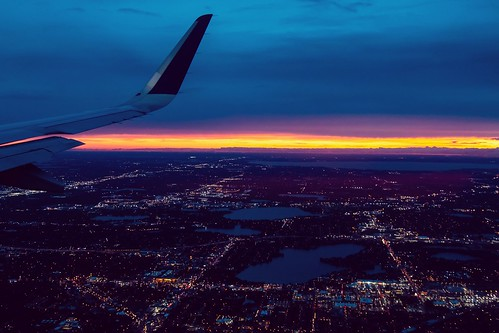 lights cityscape airplane flying clouds sunset