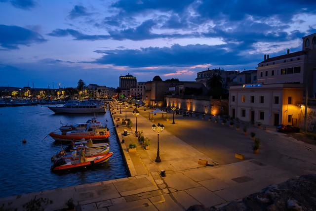 The sky lighting up at dawn over the marina in Alghero, Sardinia, Italy