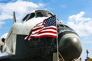 An American flag flaps proudly in the wind in front of space shuttle Atlantis on the Shuttle Landing Facility's Runway 15 at NASA's Kennedy Space Center in Florida. Original from NASA. Digitally enhanced by rawpixel.
