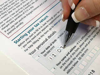 Somebody filling out the date section of a HMRC tax form | by GoSimpleTax