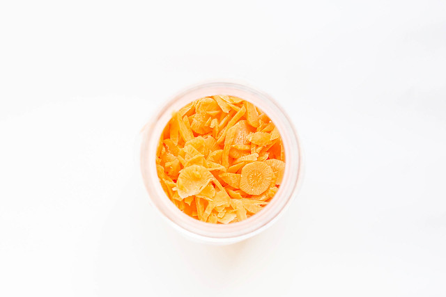 Top view of chopped carrots in jar on white background