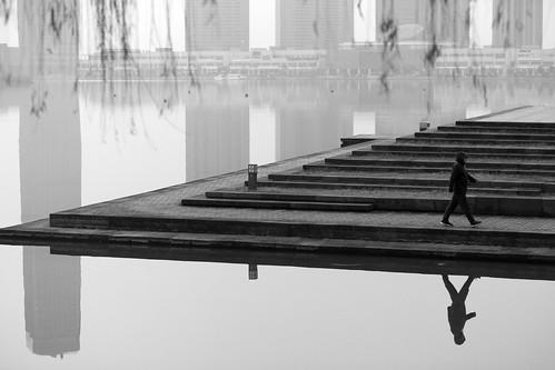 yixing wuxi jiangsu china prc sunrise dawn softlight water reflections calm mirror dongjiu lake highrise skyscrapers buildings city architecture tall blackandwhite bw mono monochrome man walking exercising