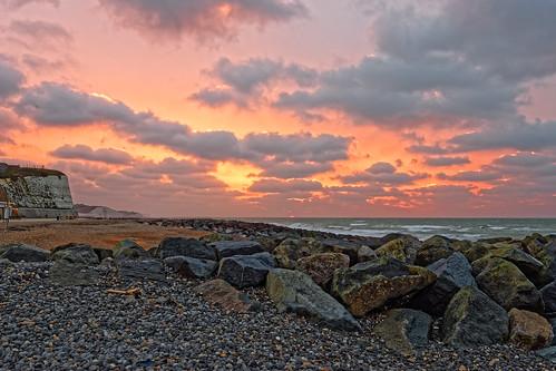beach sea ocean water rocks stones cliff chalk waves cloud sky sun sunrise dawn daybreak red yellow