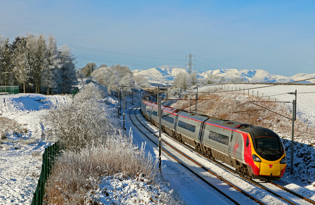 Virgin Trains Pendolino 390138 races past a snowy Docker