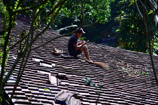 One of the work men fixing roof tiles on a building catches up on his texting! | by shankar s.