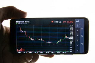 Hand holding smart phone with Ethereum chart on screen | by wuestenigel
