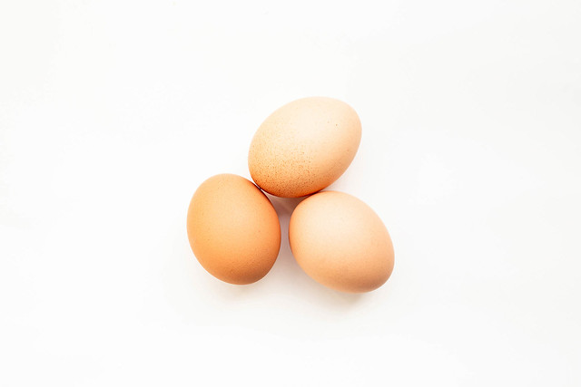 Top view of three eggs on white background