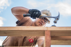 Builder 3rd Class Jesse Martinez, assigned to Naval Mobile Construction Battalion 1, Detachment Guam, hammers a purlin to the roof of a home on Tinian in December. (U.S. Navy/MC2 Kelsey J. Hockenberger)