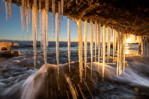 lakeontario icicles sunset wave breaking shore winter cold freezing ontario canada rock water sky clear starburst