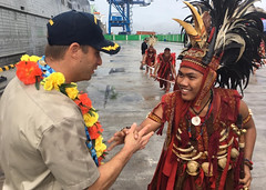 Capt. Adam Streeper, ship's master of USNS Brunswick (T-EPF 6), shakes hands with a member of a local Minahasa dance troupe after arriving in Bitung. (U.S. Navy/Cmdr. Greg Adams)