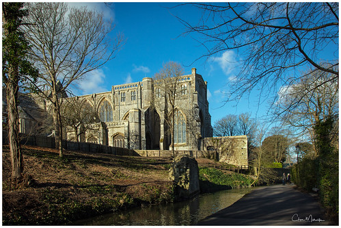 christchurch dorset uk priory trees building historic stream path clouds fence wall