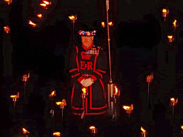 A Yeoman Warder standing among the Tower of London flames