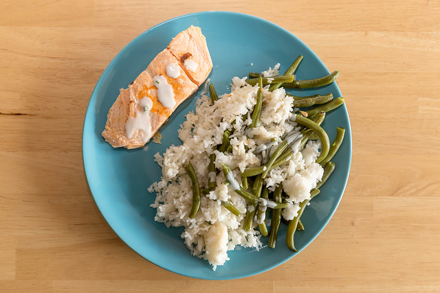 Salmon with rice and green beans on a blue plate