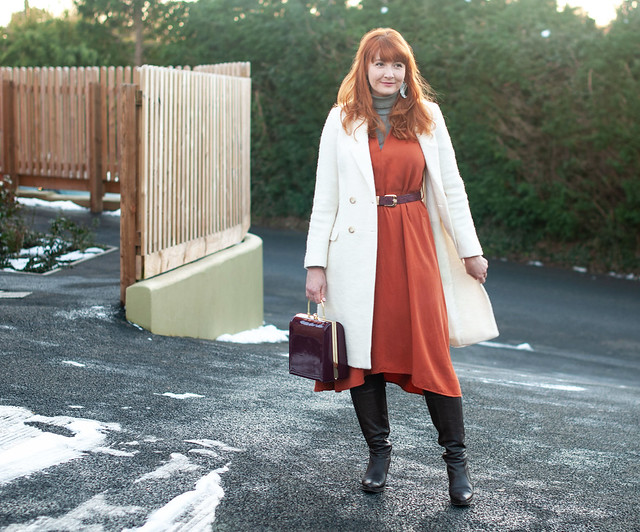 The Magic Powers of a White Winter Coat \ longline winter white wool coat \ burnt orange midi dress \ brown knee high boots \ grey roll neck   Not DRessed As Lamb, over 40 style blogger