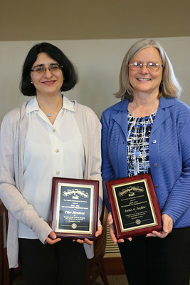Two women pose with award plaques