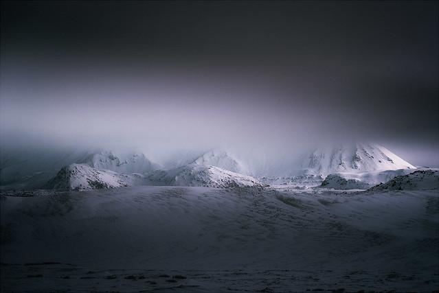 Storm Light Over Distant Peaks