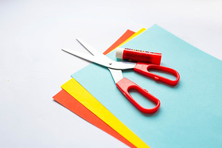 Colorful craft paper with scissors and glue on white background | by wuestenigel