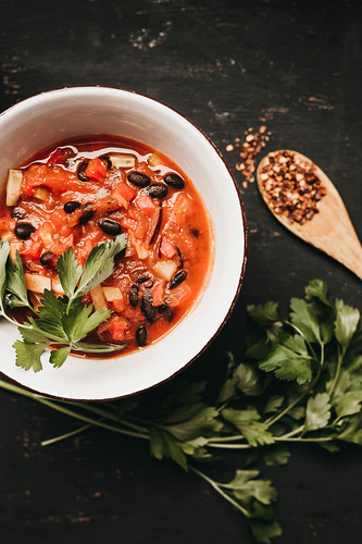Top view of bowl of black bean chili with wooden spoon and fresh parsley | by wuestenigel