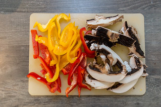 Fresh cut mushrooms with yellow and red pepper slices on a cutting boar - top view   by verchmarco
