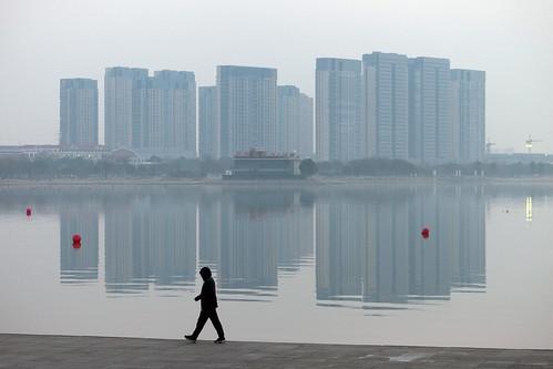 yixing wuxi jiangsu china prc sunrise dawn softlight water reflections calm mirror dongjiu lake highrise skyscrapers buildings city architecture tall man walking exercising