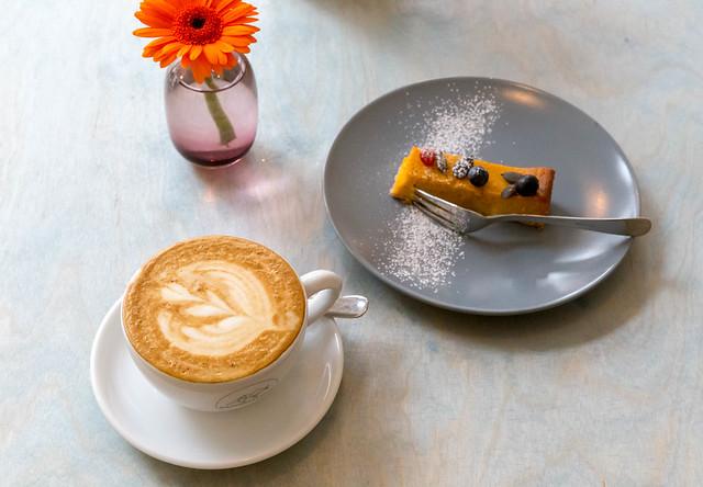 Ein Stück Kürbiskuchen mit einer Tasse Cappuccino aus frisch gerösteten Bohnen im Kaffeesaurus in Köln