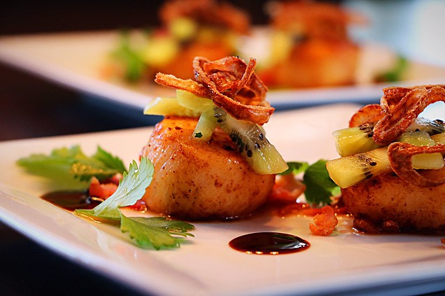 Seared scallops with fried shallots, kiwis and bacon.