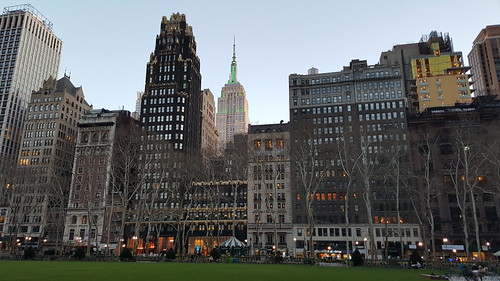 Bryant Park Hotel and the Empire State Building NHL & NHP lighting in green in honor of Earth Day as seen from Bryant Park in Midtown Manhattan in New York City, NY