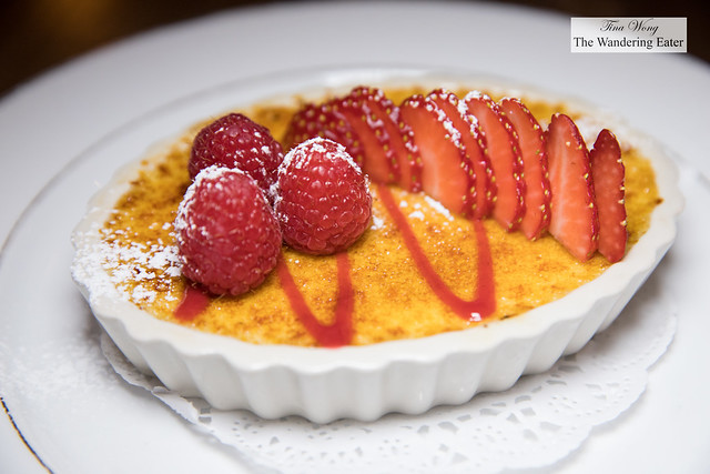 Crème brûlée topped with fresh raspberries and sliced strawberries