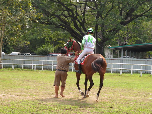 チェンマイ競馬場の合掌しながら騎乗する騎手