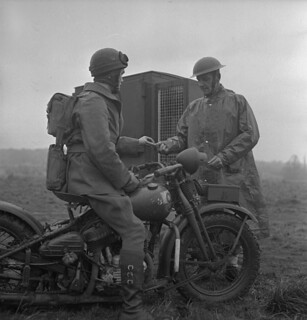 Dispatch rider Private J.W. King (left) accepts a pigeon message from Corporal J. Hanley... / Le caporal J. Hanley, du Corps royal canadien des transmissions, remet un message acheminé par un pigeon à l'estafette J. W. King...