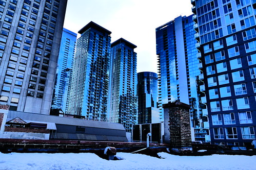 Light Layer of Rooftop Snow and Blue Glass Looming Above
