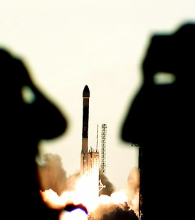 A Boeing Delta II rocket is framed between the ghostly silhouettes of two press photographers as it launches Deep Space 1 on its mission from Launch Complex 17A. Original from NASA. Digitally enhanced by rawpixel.