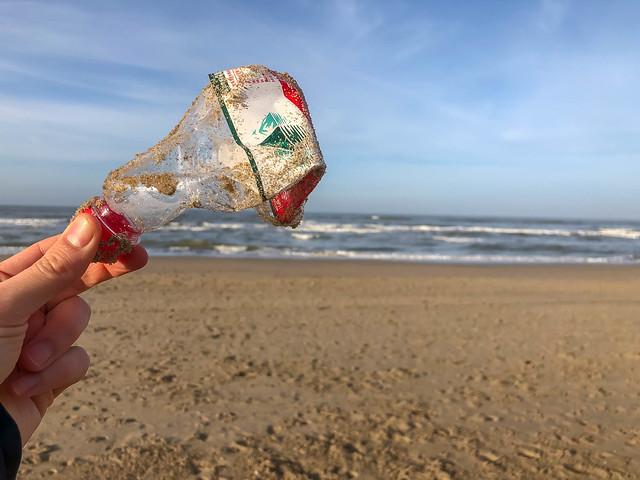Alte Einwegflasche als Plastikmüll am Zandvoort-Strand vor der Nordsee, Niederlande