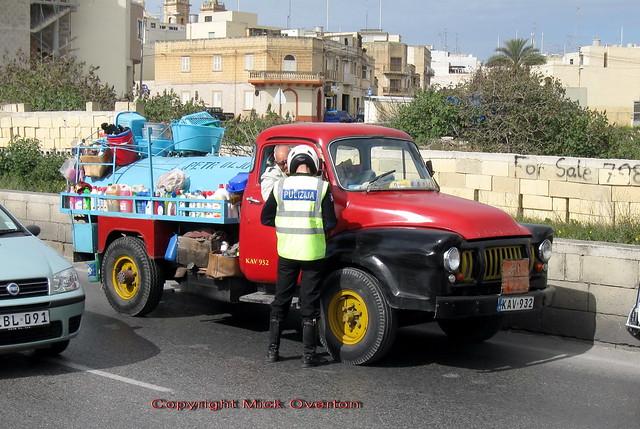 Maltese Motorcycle cop writes ticket for heating oil truck driver of Bedford J type KAV932