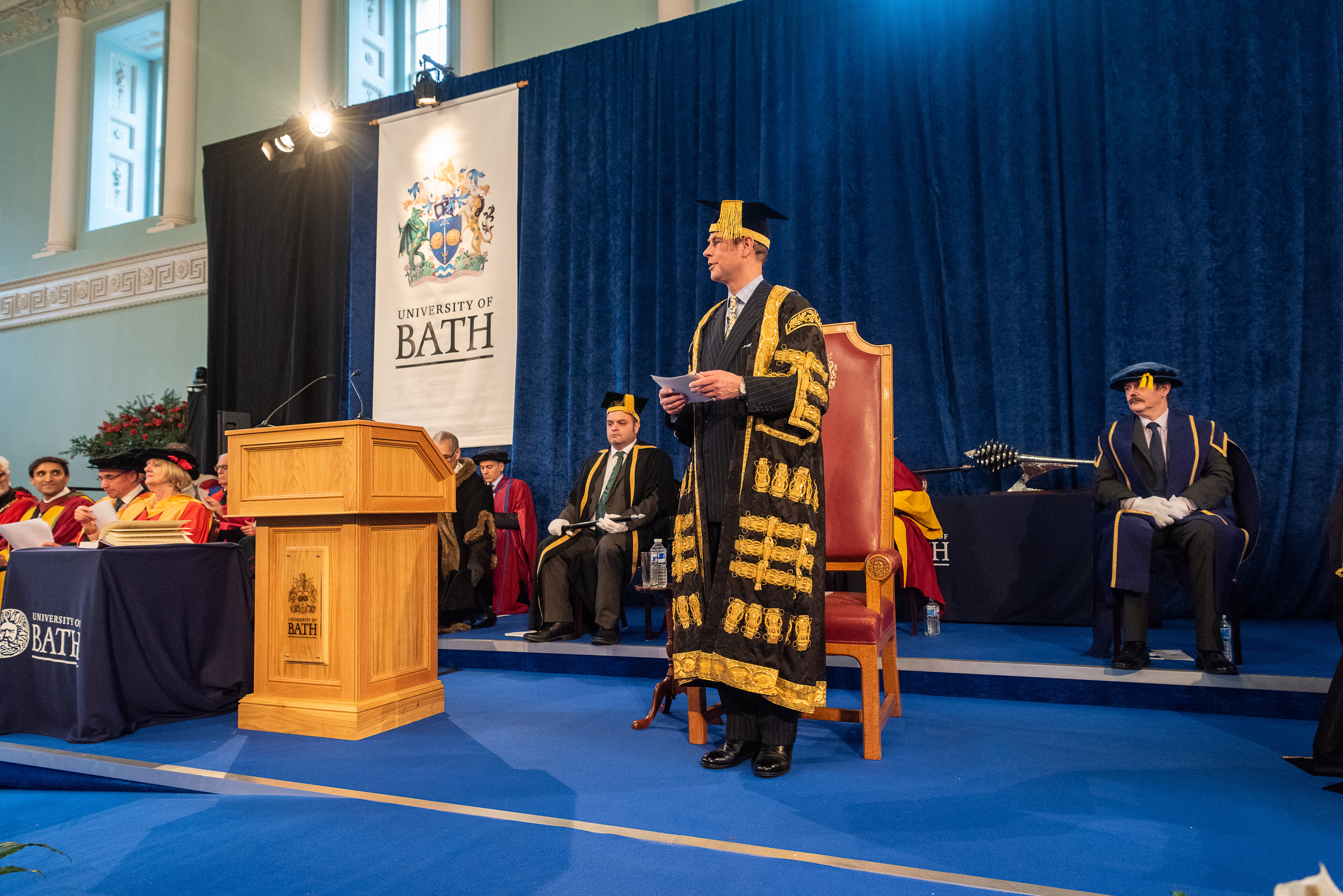 Prince Edward presiding over a graduation ceremony in his graduation outfit on a stage with dignitaries also on the stage